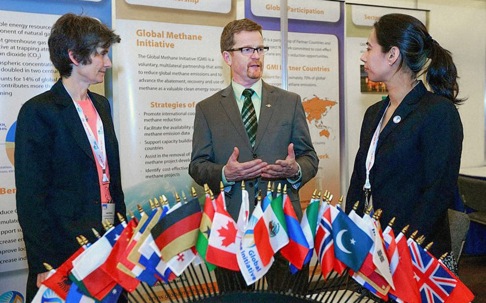 Three professionals stand and talk in front of a poster display about the Global Methane Initiative