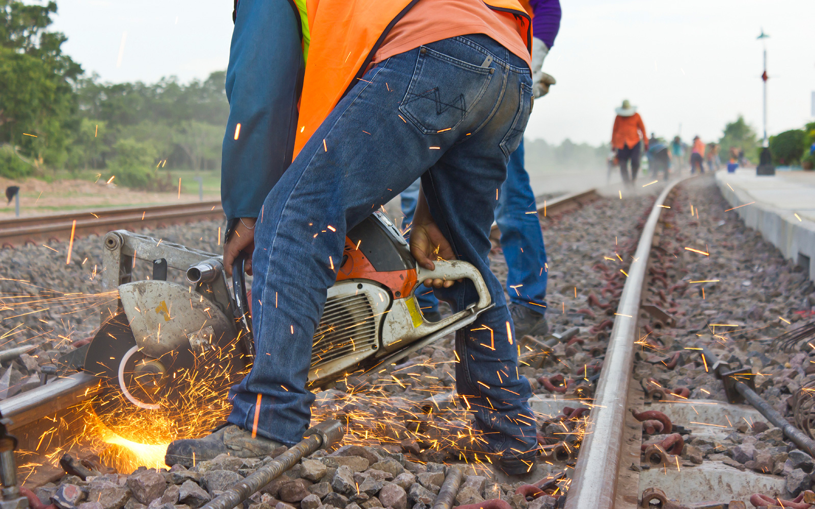 Sparks fly from a circular saw operated by a worker cutting a rail on a railway