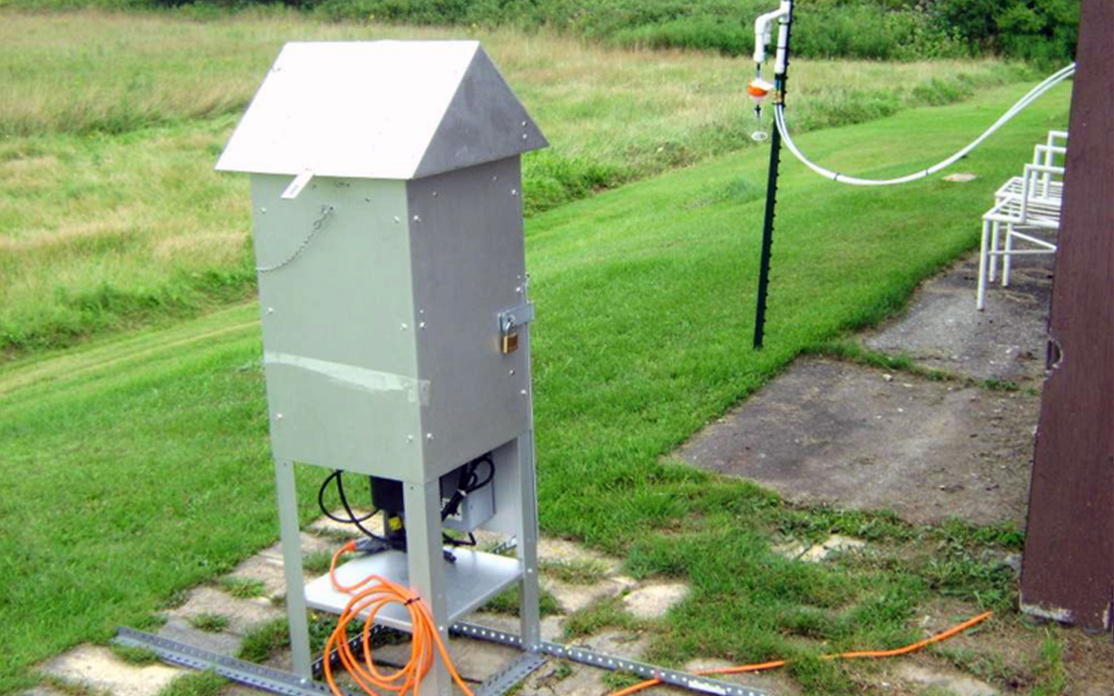 Air monitoring device situated in a yard just outside a home