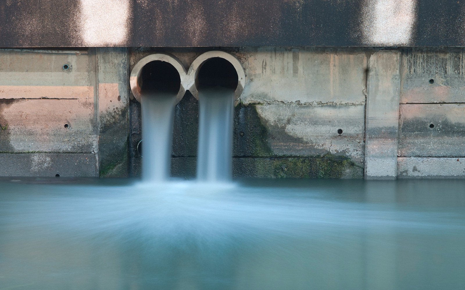 Effluent flowing from two discharge pipes into a water body