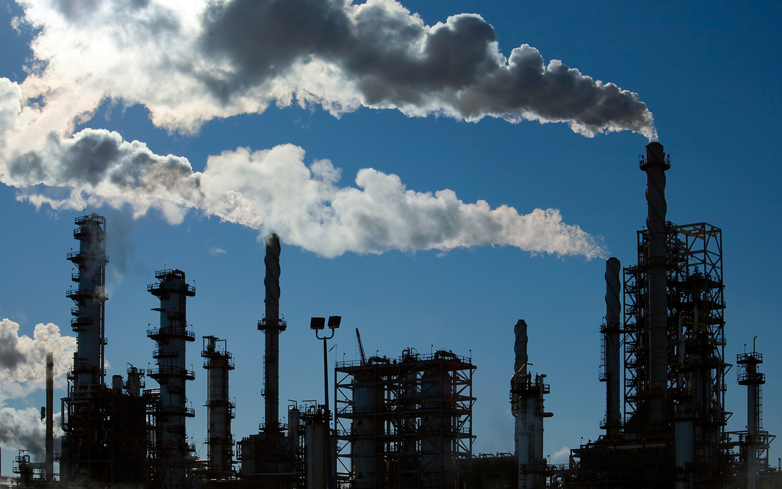 Petroleum refinery pipes with emissions pouring into the ambient air