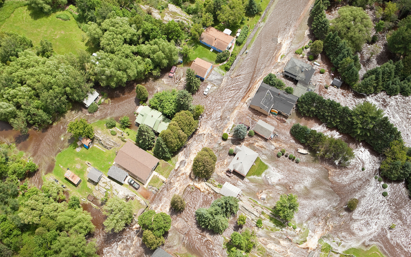 Aerial view of flood waters surging through local area with residential streets and homes.