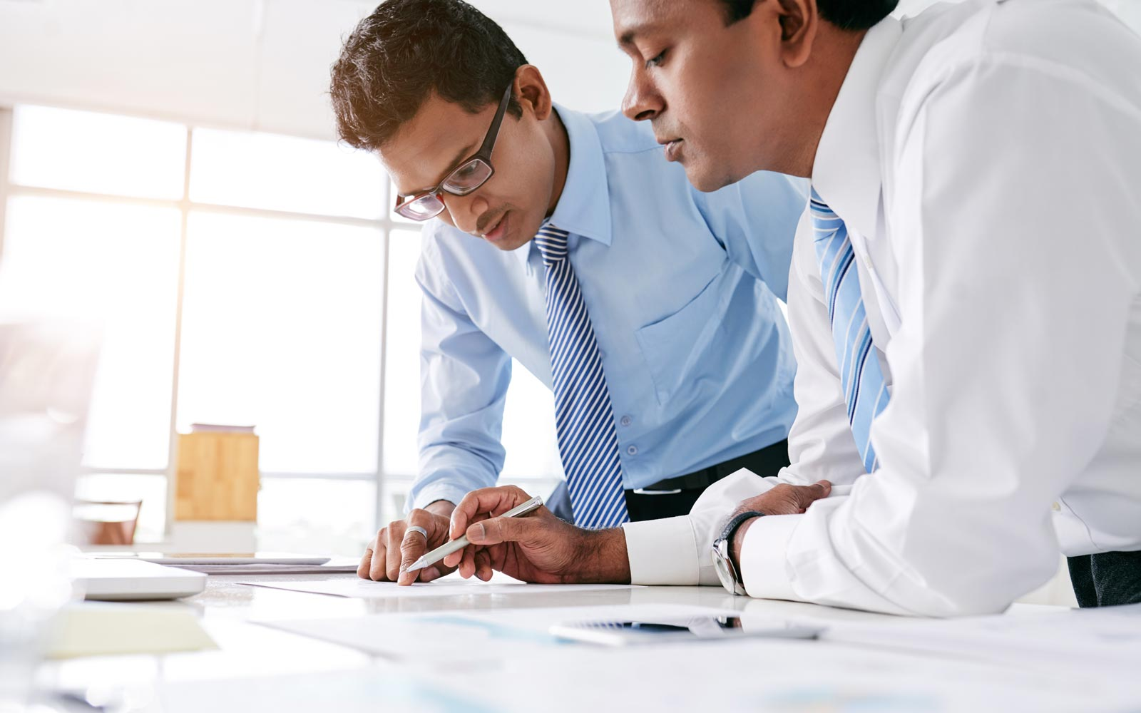 Two men standing side by side over an office table carefully examine the contents of a document open on the table.