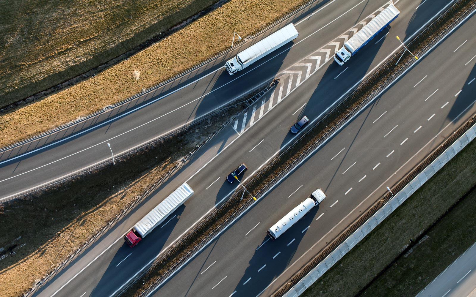 Aerial view of four freight trucks on a highway and off-ramp