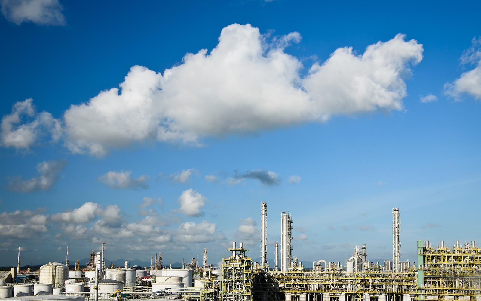Petrochemical plant below a blue sky with clouds