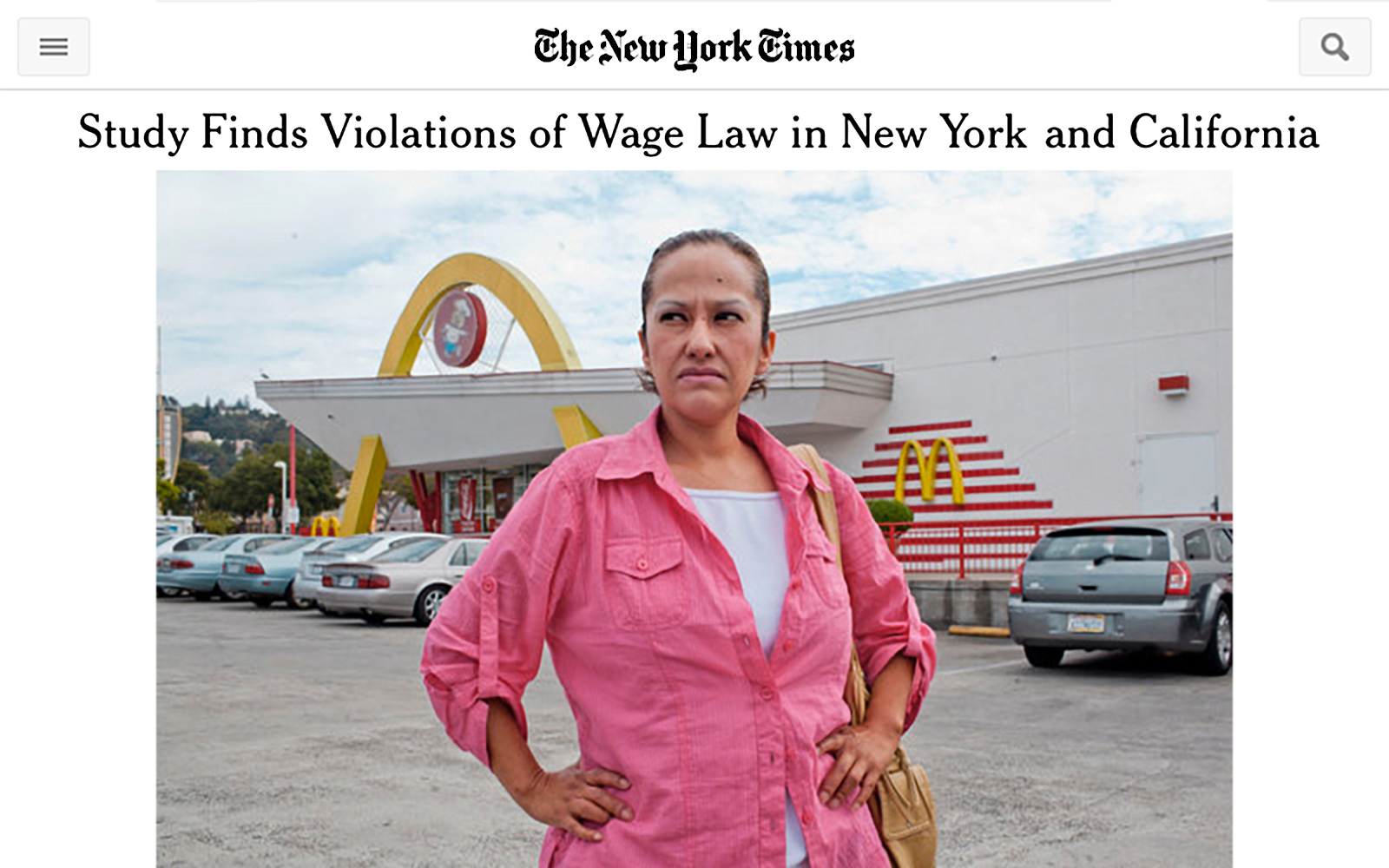 "Screenshot of online New York Times page with headline ""Study Finds Violations of Wage Law in New York and California"" and a photo of a woman standing in front of a fast food restaurant, hands on hips, looking into the distance with anger in her eyes."