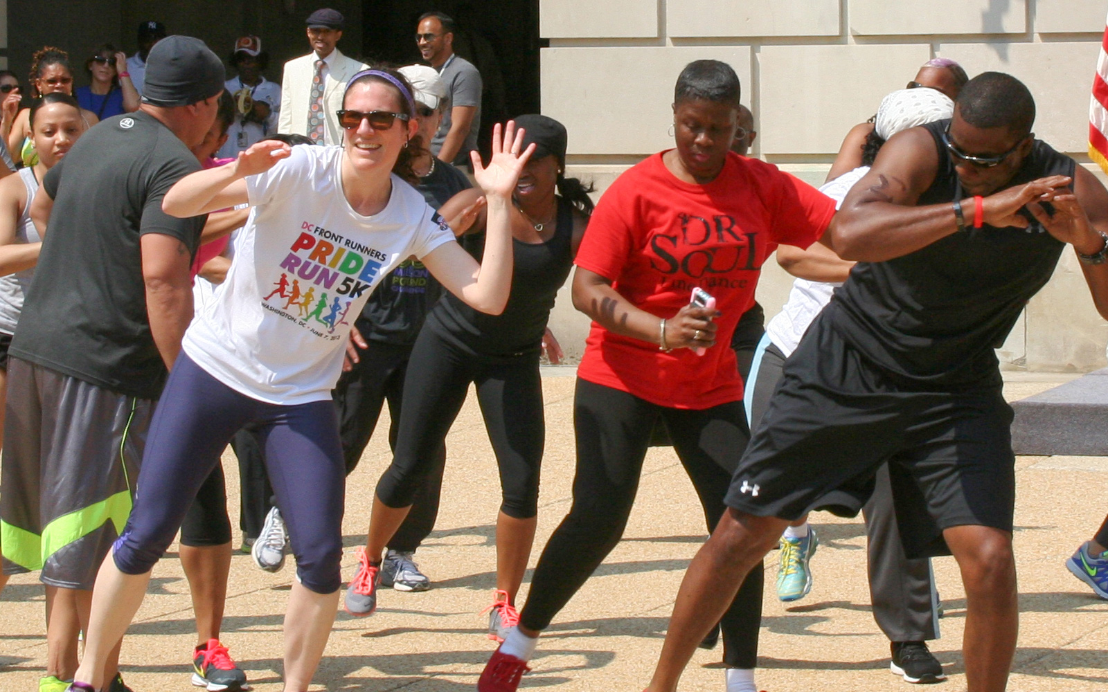 Group of EPA employees participating in outdoors synchonized aerobic dance exercises in an urban environment on a sunny day