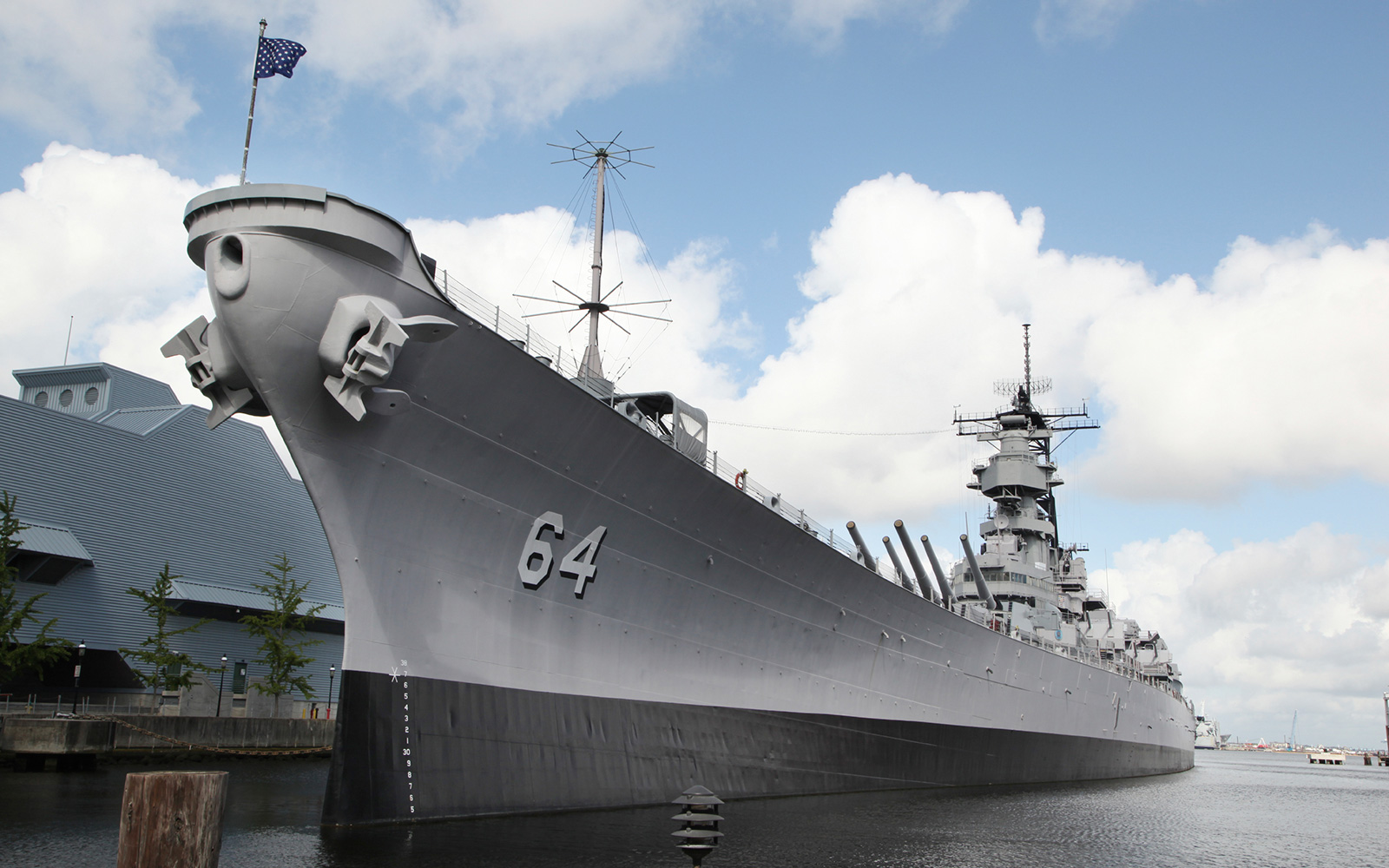 Large Navy battleship sitting dockside in water below a blue sky