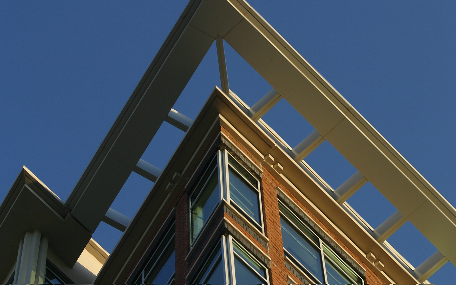The top corner of a modern building, as seen from below, with blue sky in the background