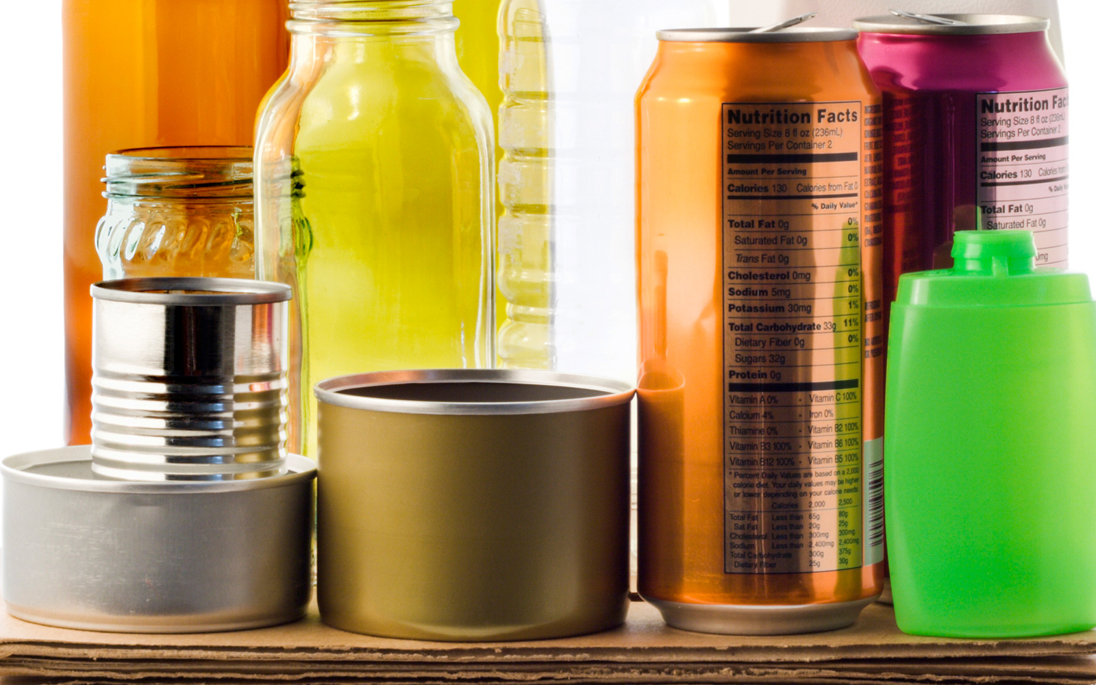 A colorful variety of different packaging types, including cans, glass jars, plastic bottles, and cardboard