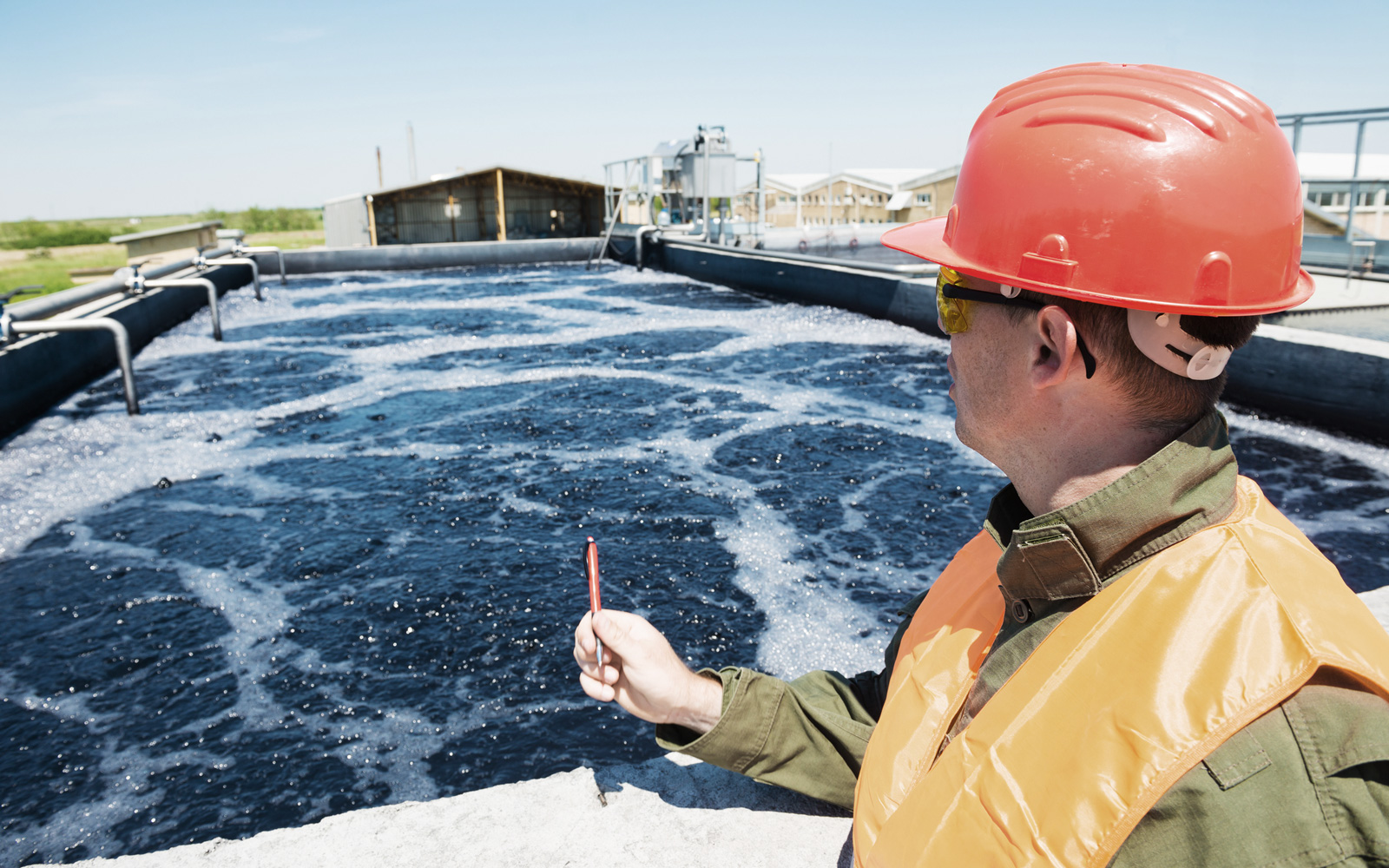 Man in hard hat and safety glasses looking at water in a wastewater treatment tank.