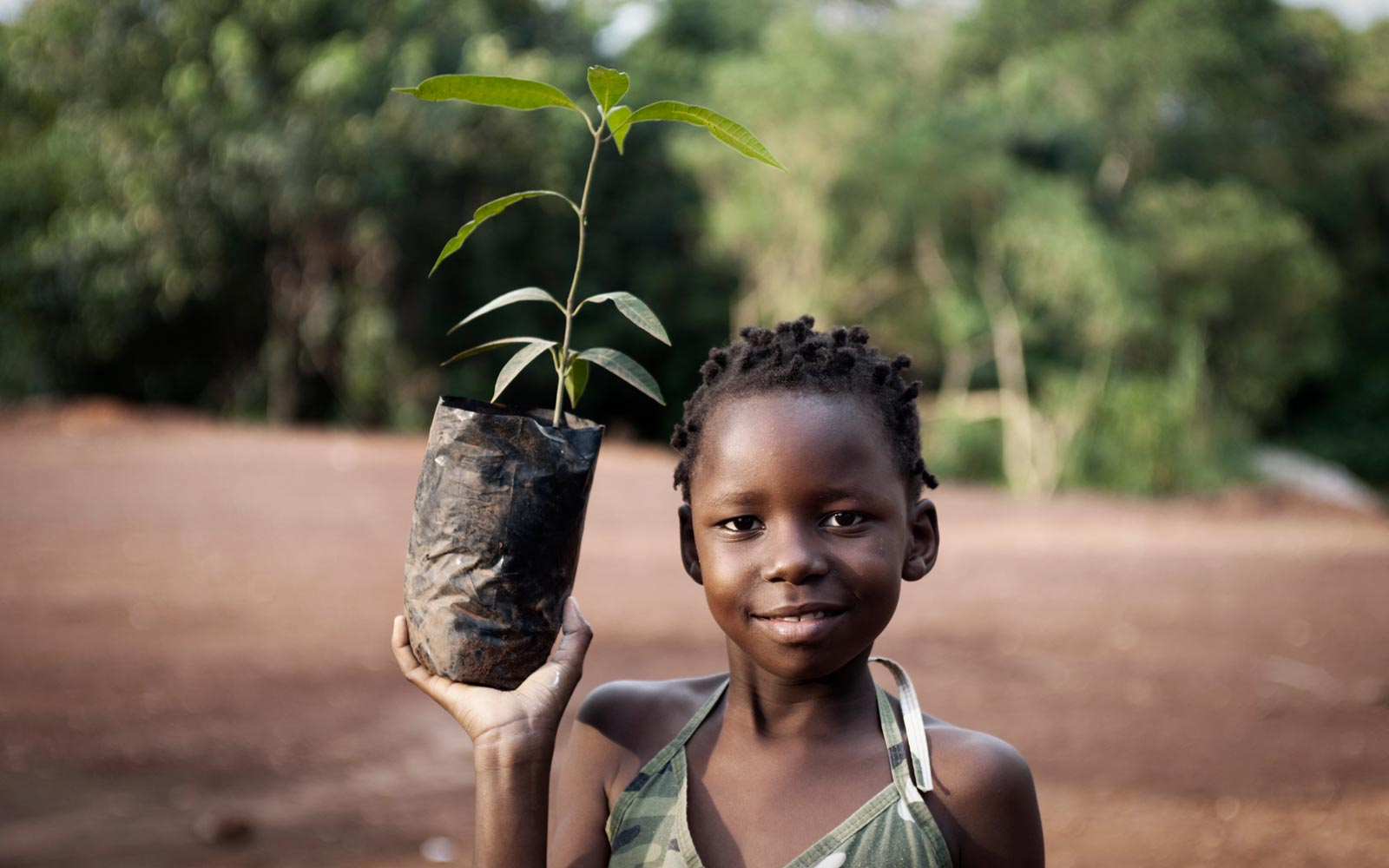 African child in a rural African setting, holding a bagged plant ready for planting.