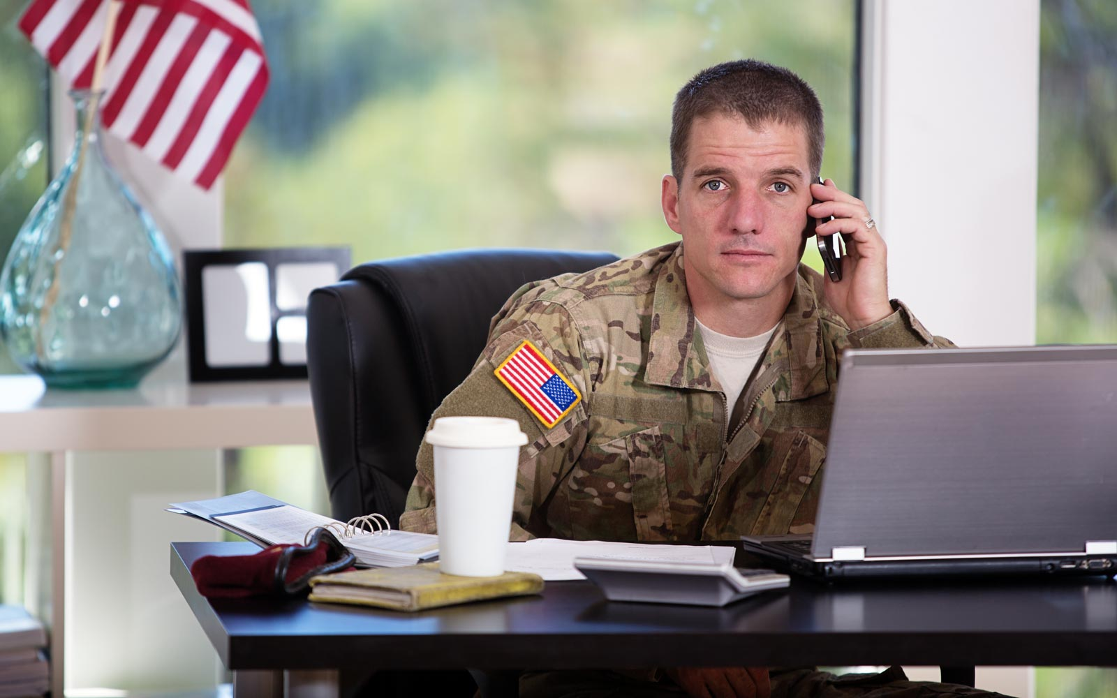 Male veteran on a phone at a work desk with an American flag in the background.