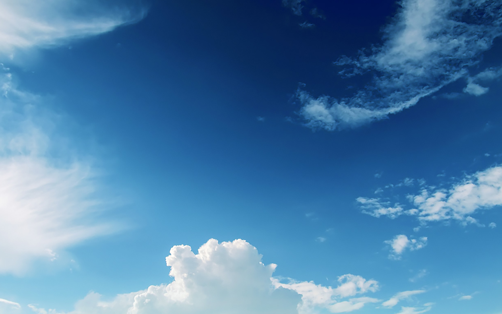 Clear blue sky with puffy white clouds