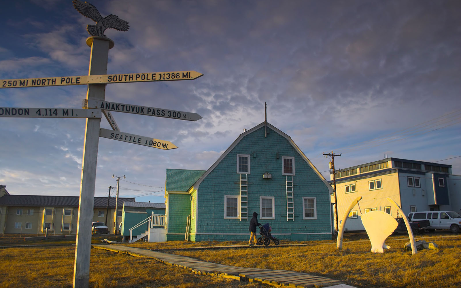 Photo of houses in Barrow, Alaska and a signpost pointing to far-away places